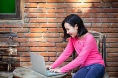 愉快亚洲女孩或学生工作,浏览有手提电脑的互联网在室外的桌上,微笑的孩子在前面坐 库存图片