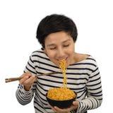 愉快亚洲妇女的感受吃方便面 免版税库存图片