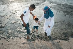 愉快亚洲家庭佩带偶然和使用与泥在泥泞的海滩 库存图片