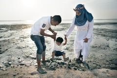 愉快亚洲家庭佩带偶然和使用与泥在泥泞的海滩 库存照片