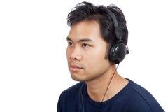 愉快亚裔的人听到与耳机的音乐 免版税图库摄影