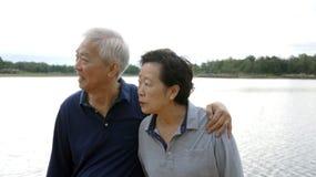 愉快亚洲资深的夫妇一起拥抱湖背景 免版税库存照片