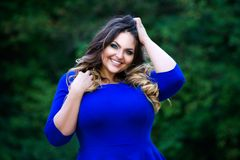 愉快加上大小在蓝色礼服户外,幸福秀丽妇女有专业构成的和发型的时装模特儿 免版税库存照片
