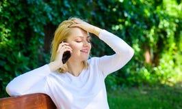 愉快听见您 女孩白肤金发的微笑的面孔谈话智能手机绿色自然背景 有的妇女宜人的交谈 库存图片