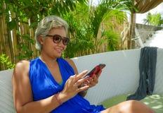 愉快和可爱的亚裔印度尼西亚妇女生活方式画象放松在快乐热带海滩胜地庭院的网络  库存图片