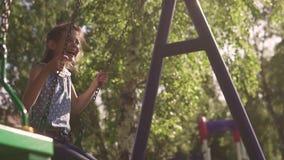愉快和无忧无虑的童年的概念 孩子在摇摆摇摆并且热心地笑 女孩一点摇摆 影视素材