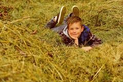 愉快和无忧无虑 愉快的男孩 小男孩愉快微笑 小男孩喜欢放松在干草 它在哪里Im最愉快 图库摄影