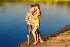 愉快和年轻人怀孕的夫妇获得在海滩的乐趣在sunse 库存照片