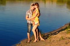 愉快和年轻人怀孕的夫妇获得在海滩的乐趣在sunse 图库摄影