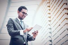 愉快商人在网上与数字片剂一起使用,当站立在一个办公室外在城市时 免版税库存图片