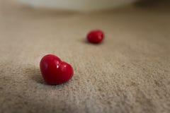 愉快在浅褐色的地毯的情人节两红色心脏 免版税库存照片