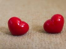 愉快在浅褐色的地毯的情人节两红色心脏 库存照片
