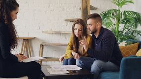 愉快地亲吻可爱的年轻夫妇房子的买家看纸并且与地产商谈话然后微笑和 股票录像