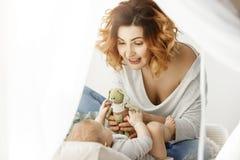 愉快地使用与她珍贵的女婴的年轻美丽的母亲在舒适大床上 给她的婴孩逗人喜爱的绿色的妇女 免版税库存照片
