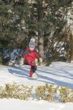 愉快地使用在雪的红色成套装备的小男孩 图库摄影