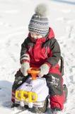 愉快地使用在雪的红色成套装备的小男孩 库存照片