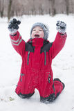 愉快地使用在雪的红色成套装备的小男孩 库存图片
