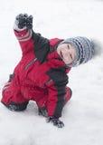 愉快地使用在雪的红色成套装备的小男孩 免版税库存照片