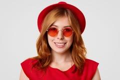 愉快地关闭相当有柔和的微笑的,神色白种人年轻女性射击在照相机,佩带红色树荫,并且帽子,高兴reci 库存图片