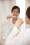愉快地刷她的牙的美丽的亚裔妇女 库存图片
