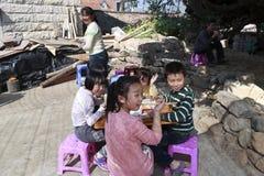 愉快地吃午餐的村民在遮篷下 库存照片