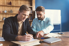 愉快地和集中做就业的两个男性在办公室测试 库存图片