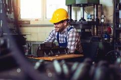 愉快地工作在他的有安全帽的车间的冶金学工作者  免版税库存照片