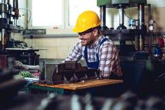 愉快地工作在他的有安全帽的车间的冶金学工作者  免版税图库摄影