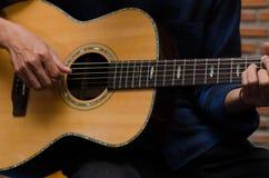 愉快地弹声学吉他的一个年轻人在音乐屋子 免版税库存照片