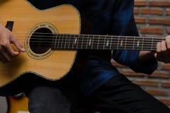 愉快地弹声学吉他的一个年轻人在音乐屋子 免版税图库摄影