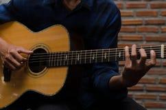 愉快地弹声学吉他的一个年轻人在音乐屋子 库存图片