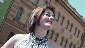 愉快地微笑在夏天礼服的老镇的俏丽的女孩 股票录像