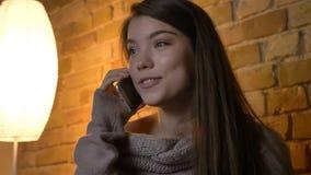 愉快地微笑年轻俏丽的白种人的女性特写镜头射击拜访电话和,当基于在a时的沙发 库存图片