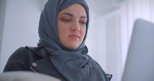 愉快地微笑年轻可爱的回教的女实业家特写镜头画象hijab的使用看照相机的膝上型计算机 影视素材