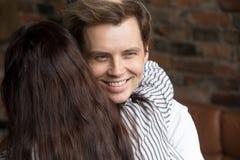 愉快地微笑年轻狡猾的说谎者的人,当拥抱他时的妇女 图库摄影