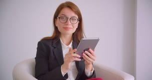愉快地微笑年轻白种人的女实业家特写镜头画象发短信在片剂的玻璃的看ta照相机 股票录像