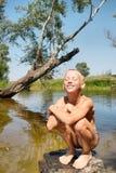 愉快地微笑的男孩坐岩石在湖 免版税图库摄影