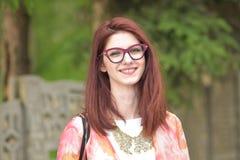 愉快地微笑美丽的年轻红头发人的妇女 免版税库存图片