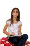 愉快地执行女孩她的家庭作业年轻人 库存照片