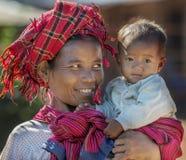 愉快地抱她的她的胳膊的Intha部族妇女孩子, Inle缅甸 库存照片