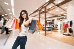 愉快地拿着购物袋的亚裔妇女和微笑,百货商店或者购物中心迷离背景与拷贝空间 免版税图库摄影