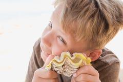 愉快地拿着黄海壳的滑稽的被晒黑的男孩 图库摄影