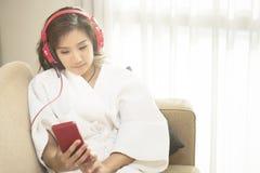 愉快地演奏电话的美丽的妇女在卧室在早晨 图库摄影