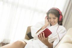 愉快地演奏电话的美丽的妇女在卧室在早晨 免版税库存图片