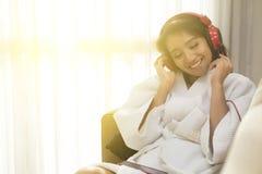 愉快地演奏电话的美丽的妇女在卧室在晚上 库存照片