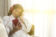 愉快地演奏电话的美丽的妇女在卧室在晚上 免版税图库摄影