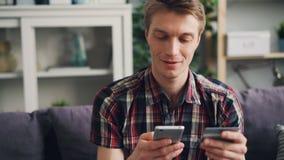 愉快地然后微笑快乐的年轻人付与接触智能手机屏幕的万一银行卡的网上付款 财务 股票视频