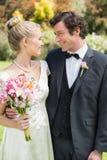 愉快地看彼此的可爱的新婚佳偶 免版税库存照片