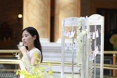 愉快地穿一件白色礼服的亚裔妇女起来她顶头微笑看 库存照片