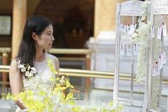 愉快地穿一件白色礼服的亚裔妇女起来她顶头微笑看 免版税库存图片